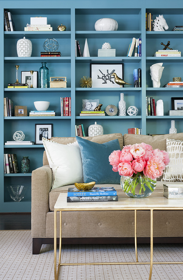Wonderful colored shelving adds life and vibrancy to this Colonial living room